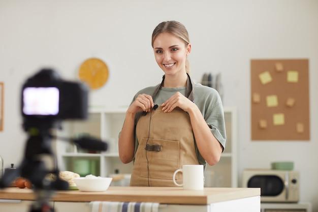 Souriante jeune femme attachant le microphone à son tablier, elle se prépare pour la vidéo en se tenant debout dans la cuisine