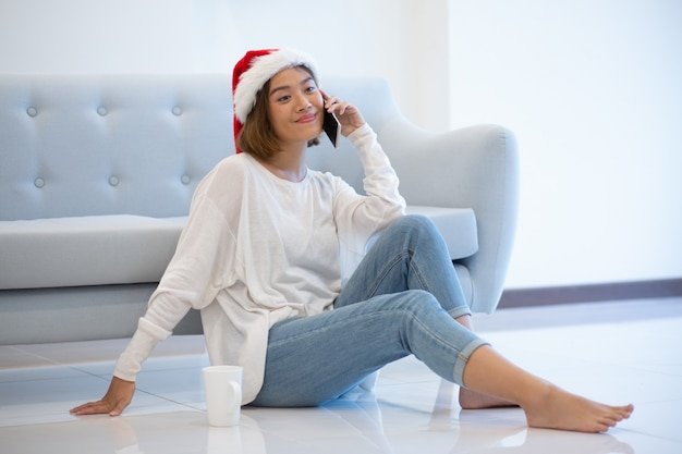 Souriante jeune femme attirante au bonnet de noel à l'aide de téléphone portable