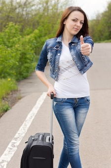 Souriante jeune femme attirante donnant un coup de pouce