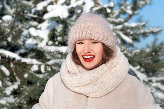 Souriante jeune femme au chapeau volumineux et écharpe en hiver à l'extérieur.