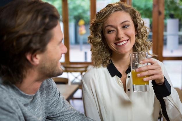 Souriante jeune femme ayant du jus tout en regardant l'homme dans un café