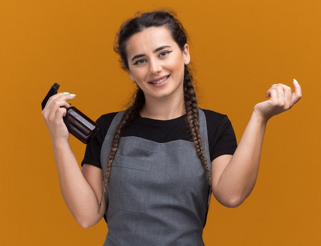 Souriante jeune femme barbier en uniforme tenant un vaporisateur répandant la main isolée sur un mur orange