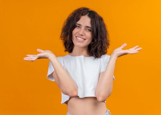 Souriante jeune femme belle montrant les mains vides sur un mur orange isolé