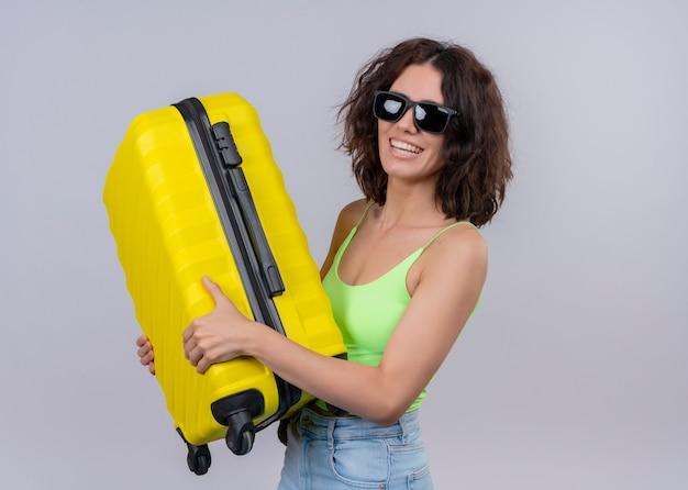 Souriante jeune femme belle voyageur portant des lunettes de soleil et tenant la valise sur un mur blanc isolé