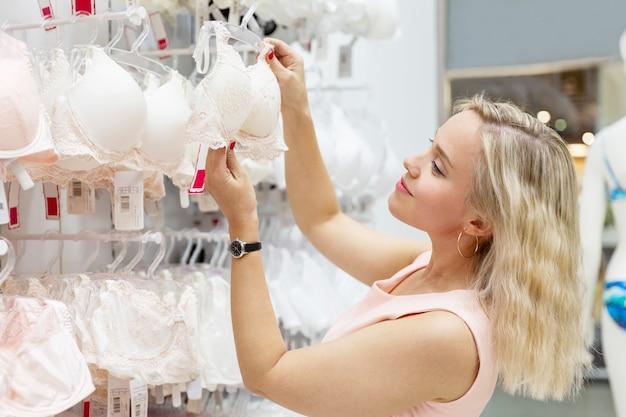Souriante jeune femme blonde choisit des sous-vêtements dans le magasin. féminité et sexualité.