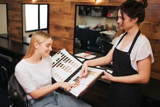 Souriante jeune femme blonde et coiffeur choisissant la couleur des cheveux de la palette