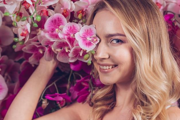 Souriante jeune femme blonde couvrant ses yeux avec une branche d'orchidée rose