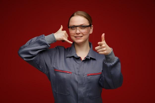 Souriante jeune femme blonde ingénieur portant des lunettes de sécurité et uniformes faisant appel geste pointant vers la caméra
