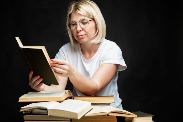 Souriante jeune femme blonde lit dans des verres avec un tas de livres. éducation, connaissances et loisirs.