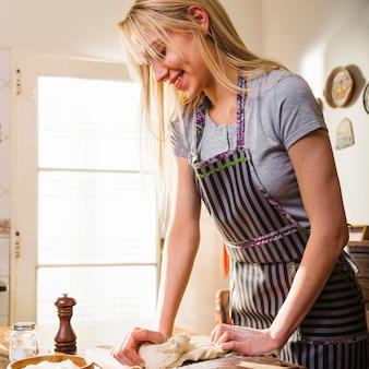 Souriante jeune femme blonde, pétrir la pâte sur une planche à découper à la maison