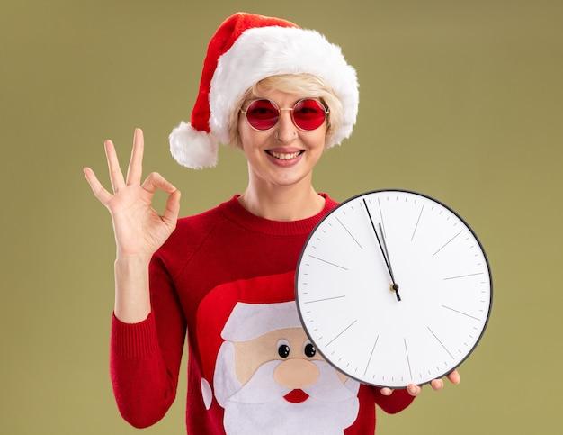 Souriante jeune femme blonde portant un chapeau de noël et un pull de noël du père noël avec des lunettes tenant une horloge regardant faire un signe ok isolé sur un mur vert olive