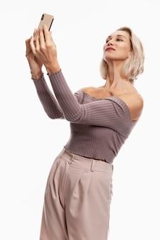 Souriante jeune femme blonde à prendre des photos d'elle-même au téléphone. fond blanc.