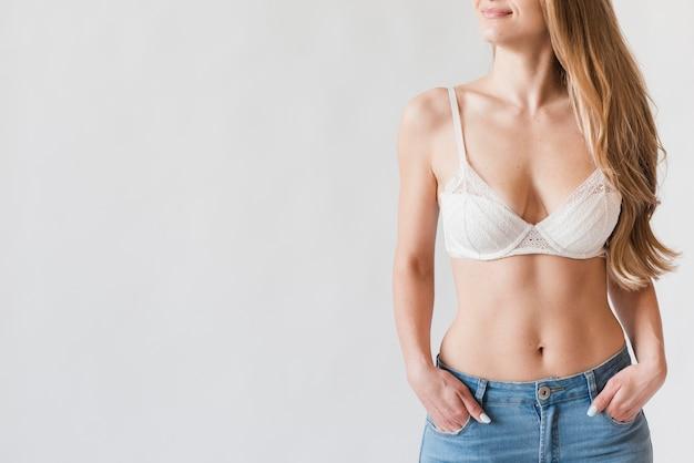 Souriante jeune femme blonde qui pose en soutien-gorge et jeans