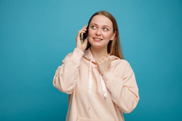 Souriante jeune femme blonde regardant au coin du col de son sweat-shirt parler au téléphone