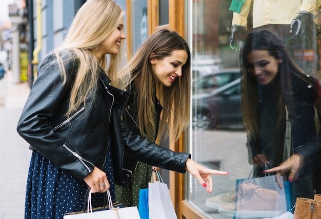 Souriante jeune femme blonde en regardant son amie pointant vers des chaussures dans la vitrine