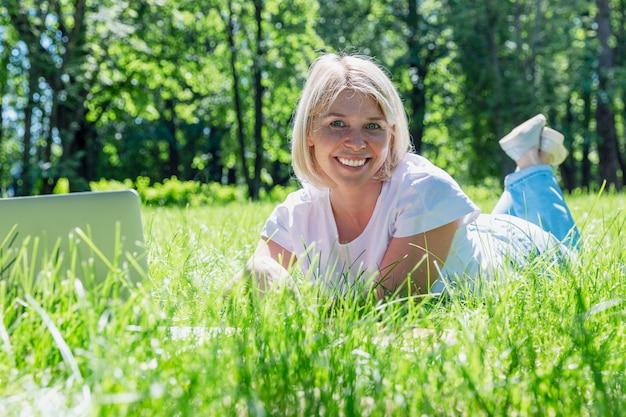 Souriante jeune femme blonde se trouve sur l'herbe dans un parc avec un ordinateur portable sur une journée ensoleillée d'été.