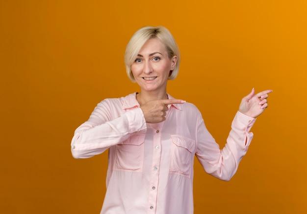 Souriante jeune femme blonde slave sur le côté isolé sur un mur orange avec espace de copie