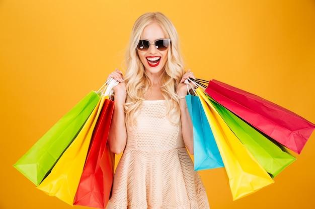 Souriante jeune femme blonde tenant des sacs à provisions.