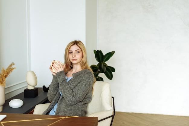 Souriante jeune femme blonde tenant une tasse de thé