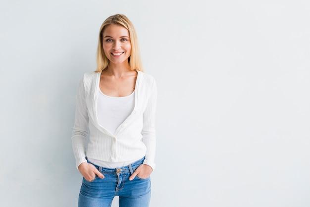 Souriante jeune femme blonde en vêtements décontractés