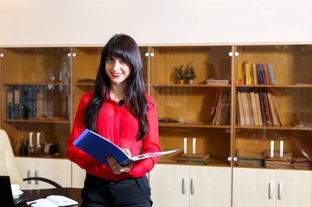 Souriante jeune femme en blouse rouge avec un dossier de documents