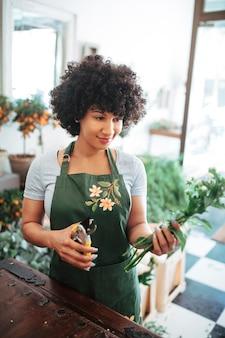 Souriante jeune femme avec bouquet de fleurs