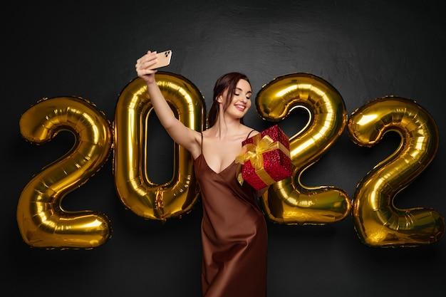 Souriante jeune femme brune en robe élégante faisant selfie sur smartphone sur fond noir doré...