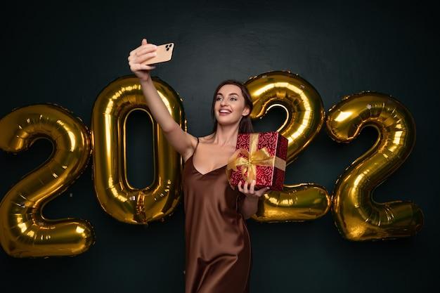 Souriante jeune femme brune en robe élégante faisant selfie sur téléphone mobile avec boîte cadeau rouge sur noir...