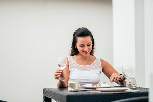 Souriante jeune femme buvant un verre de vin et ayant un morceau de gâteau.