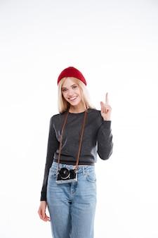 Souriante jeune femme casual jeune pointant le doigt vers le haut