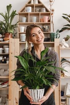 Souriante jeune femme céramiste tenant une plante.