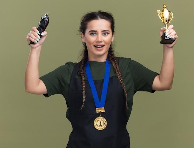 Souriante jeune femme coiffeur en uniforme et médaille soulevant la coupe du gagnant avec des tondeuses à cheveux isolé sur mur vert olive