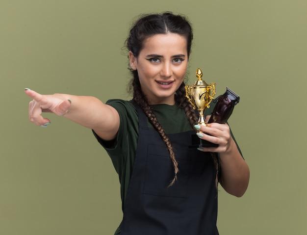 Souriante jeune femme coiffeur en uniforme tenant une tondeuse à cheveux avec des points de coupe gagnant sur le côté isolé sur mur vert olive
