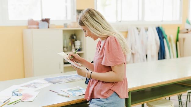 Souriante jeune femme à colorier au crayon dans l'atelier