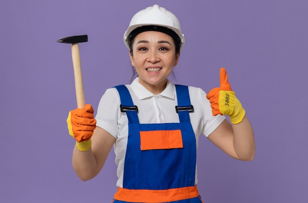 Souriante jeune femme de constructeur asiatique avec un casque de sécurité blanc et des gants tenant un marteau et le pouce vers le haut