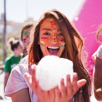 Souriante jeune femme avec la couleur holi sur son visage, tenant la mousse à la main en regardant la caméra
