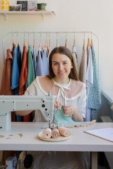 Souriante jeune femme cousant des vêtements dans son propre atelier ou atelier