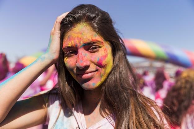 Souriante jeune femme a couvert son visage avec la couleur holi