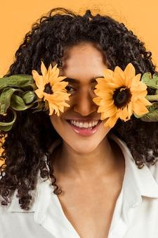 Souriante jeune femme couvrant le visage avec des fleurs
