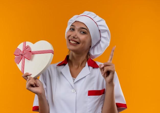 Souriante jeune femme cuisinier portant l'uniforme de chef tenant la forme de coeur pointe le doigt vers le haut sur fond orange isolé