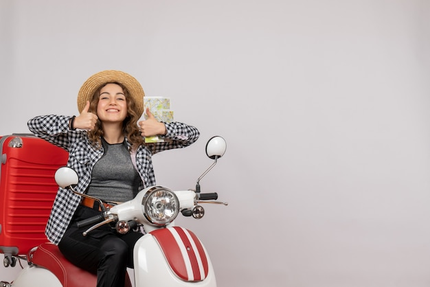 Souriante jeune femme sur cyclomoteur holding card making thumbs up sign on gray
