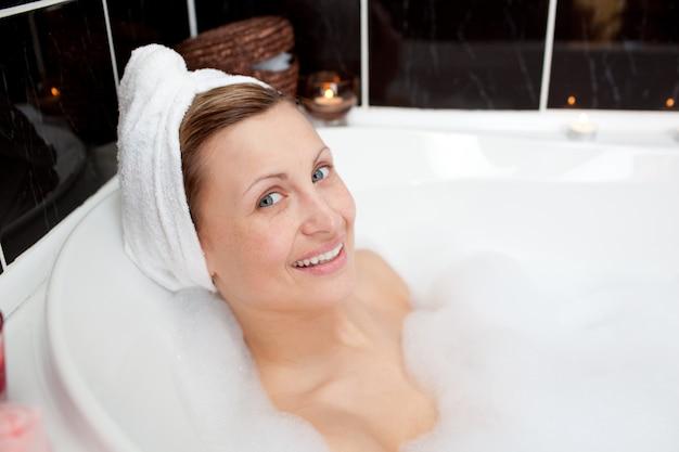 Souriante jeune femme dans un bain moussant