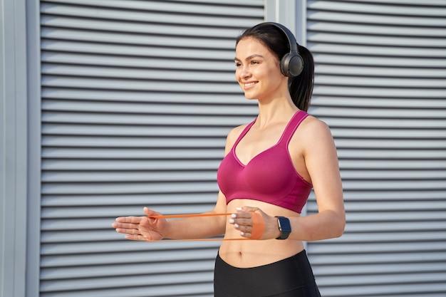Souriante jeune femme dans des écouteurs sans fil à l'aide d'élastiques de fitness. notion de sport. espace de copie