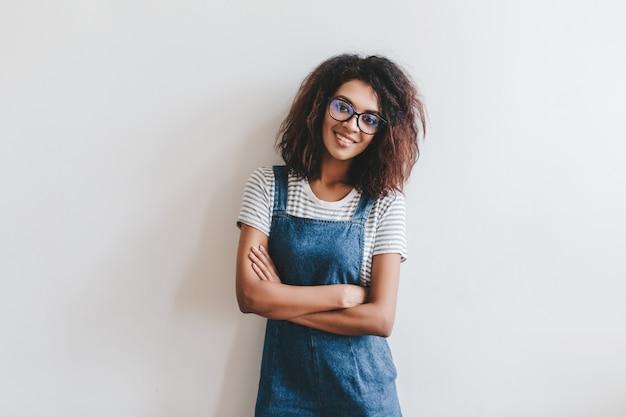 Souriante jeune femme dans des verres aux cheveux brun foncé posant les bras croisés devant un mur de lumière