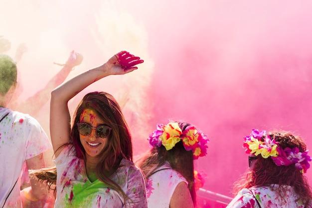 Souriante jeune femme dansant dans la couleur holi