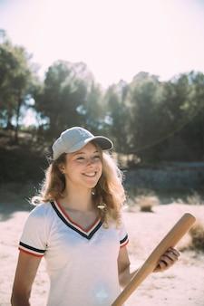 Souriante jeune femme debout avec une batte de baseball