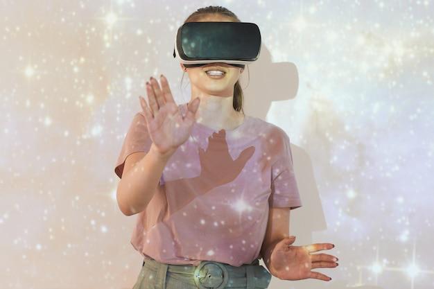Souriante jeune femme debout contre l'écran de projection avec ciel étoilé scintillant tout en étudiant l'astronomie avec simulateur de réalité virtuelle