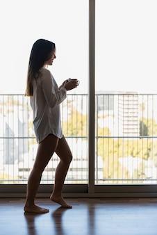 Souriante jeune femme debout dans un balcon tenant une tasse de café