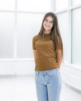 Souriante jeune femme debout dans un bureau lumineux