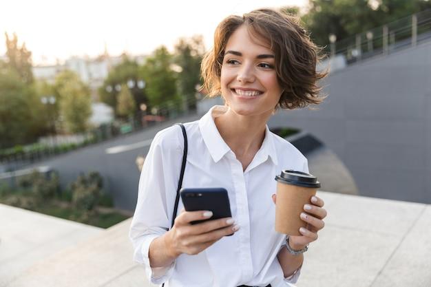 Souriante jeune femme debout dans la rue